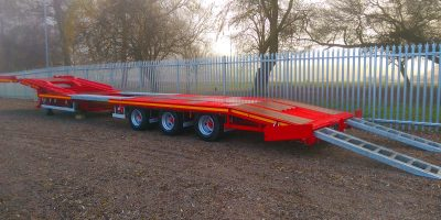 Drop frame extending tractor carrier with multi load pivot ramp